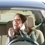 Woman with lipstick and cell phone in the car